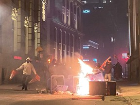 People take part in an anti-curfew protest in Montreal on Sunday April 11, 2021.