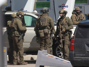 In this file photo taken April 19, 2020, members of the RCMP tactical unit confer after the suspect in a deadly shooting rampage was neutralized at the Big Stop near Elmsdale, Nova Scotia.