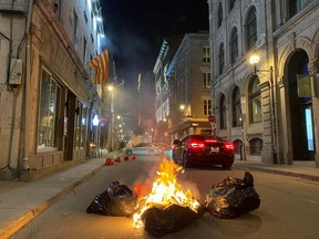 People take part in an anti-curfew protest in Montreal on Sunday April 11, 2021. Hundreds of people gathered in Old Montreal tonight in defiance of a new 8 p.m. curfew.