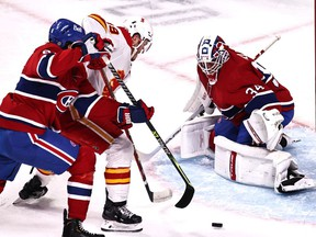 Apr 16, 2021; Montreal, Quebec, CAN; Montreal Canadiens goaltender Jake Allen (34) makes a save against Calgary Flames left wing Matthew Tkachuk (19) as defenseman Ben Chiarot (8) defends during the first period at Bell Centre. Mandatory Credit: Jean-Yves Ahern-USA TODAY Sports ORG XMIT: IMAGN-445595