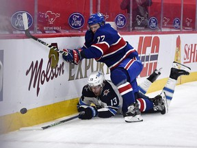 Winnipeg Jets forward Pierre-Luc Dubois (13) and Canadiens defenceman Brett Kulak (77) battle for the puck during the first period at the Bell Centre on Saturday, April 10, 2021, in Montreal.