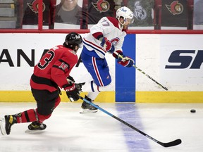 Canadiens defenceman Brett Kulak skates with the puck as he's chased by Senators forward Nick Paul in the third period.