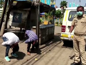Two men are seen being punished by police in Mumbai, India, for breaking COVID-19 rules.
