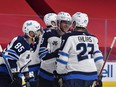 Winnipeg Jets forward Andrew Copp (9) celebrates with forward Mathieu Perreault (85) and forward Nikolaj Ehlers (27) after scoring a goal against the Montreal Canadiens during the third period at the Bell Centre in Montreal on Saturday, April 10, 2021.