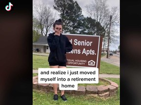 """Madison Kohout, 19, poses in front of the """"Senior Citizens Apartments"""" sign outside her home in a TikTok video."""
