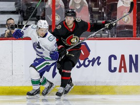 Ottawa Senators centre Josh Norris (right) checks Vancouver Canucks centre Matthew Highmore during third period NHL action at the Canadian Tire Centre, April 26, 2021.