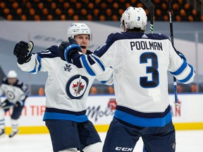 Winnipeg Jets' Tucker Poolman (3) celebrates a goal with teammates on Edmonton Oilers' goaltender Mike Smith (41) during the second period of NHL North Division playoff action at Rogers Place in Edmonton, on Wednesday, May 19, 2021.