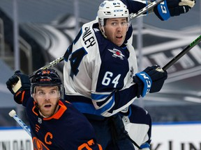 Edmonton Oilers' Connor McDavid (97) battles Winnipeg Jets' Logan Stanley (64) during the third period of NHL North Division playoff action at Rogers Place in Edmonton, on Wednesday.