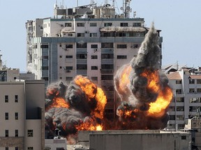 A ball of fire erupts from the Jala Tower as it is destroyed in an Israeli airstrike in Gaza city controlled by the Palestinian Hamas movement, on May 15, 2021.