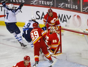 Calgary Flames goalie Jacob Markstrom is scored on by Winnipeg Jets Adam Lowry in first period NHL action at the Scotiabank Saddledome in Calgary on Wednesday, May 5, 2021.
