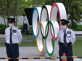 Security guards keep watch next to the Olympic Rings while people take part in a protest against the hosting of the 2020 Tokyo Olympic Games on May 18, 2021.