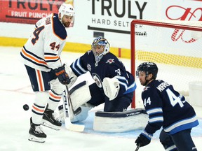 Winnipeg Jets goaltender Connor Hellebuyck tracks a shot with Edmonton Oilers forward Zach Kassian lurking in Game 3 of a Stanley Cup playoff series in Winnipeg on Sun., May 23, 2021.