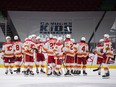 Calgary Flames players celebrate the team's overtime win against the Vancouver Canucks at Rogers Arena in Vancouver on Sunday, May 16, 2021.