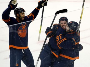 The Edmonton Oilers' Connor McDavid (97) celebrates his 100th point with Leon Draisaitl (29) and Darnell Nurse (25) against the Vancouver Canucks at Rogers Place in Edmonton on May 8, 2021.