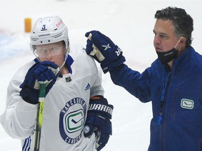 Rookie defenceman Jack Rathbone gets training-camp guidance from Canucks coach Travis Green.
