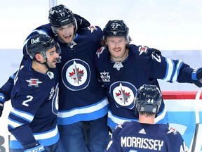 Winnipeg Jets forward Mason Appleton (left) is congratulated on his goal against the Edmonton Oilers in Game 4 of a Stanley Cup playoff series in Winnipeg by Dylan DeMelo, Adam Lowry and Josh Morrissey (from left) on Monday, May 24, 2021.