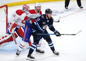 Pierre-Luc Dubois of the Winnipeg Jets jockeys for space in front of Joel Edmundson and goalie Carey Price during Game 2.
