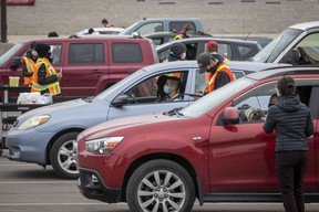 People sit in their vehicles while they wait to receive a COVID-19 vaccine at a drive-thru clinic at Richardson Stadium in Kingston, Ont., on Friday, May 28, 2021.