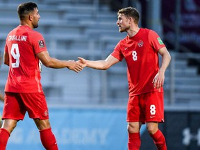 Canada striker Lucas Cavallini, (No. 9) is congratulated by teammate David Wotherspoon (No. 8) after scoring against Aruba in a FIFA 2022 World Cup Qualifying match in Bradenton, Fla., on June 5, 2021. Canada won 7-0.