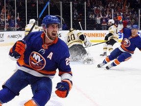 Brock Nelson, left, of the New York Islanders scores against the Boston Bruins at 5:20 of the second period in Game Six of the Second Round of the 2021 NHL Stanley Cup Playoffs at the Nassau Coliseum on June 9, 2021 in Uniondale, N.Y.