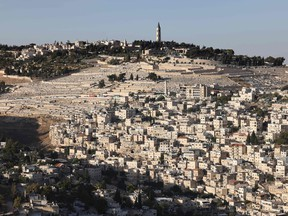 A picture taken on June 3, 2021, shows the predominantly Arab neighbourhood of Silwan, just outside the Old City in Israeli-annexed east Jerusalem, and the Jewish cemetary of Mount of Olives.