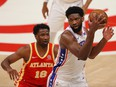 Joel Embiid of the Philadelphia 76ers catches a pass against Solomon Hill of the Atlanta Hawks during the first half of Game 3 of the Eastern Conference Semifinals at State Farm Arena on June 11, 2021 in Atlanta, Ga.