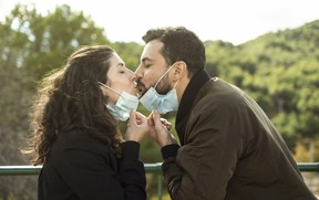Couple kisses outdoors with a surgical mask. Outdoor portrait symbolizing pandemic love