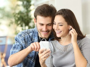 Happy couple sharing music from smart phone sitting on a couch at home.