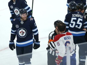 Winnipeg Jets centre Pierre-Luc Dubois (left) yells at Shea Weber as Montreal Canadiens defenceman looks for a piece of Jets centre Mark Scheifele during Game 1 of their division final.