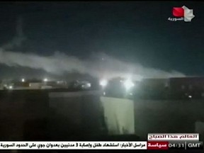 In this image grab taken from a broadcast by Syria TV on Monday, June 28, 2021, shows smoke billowing from a facility used by Iran-backed groups following U.S. air strikes on the Syrian-Iraqi border.