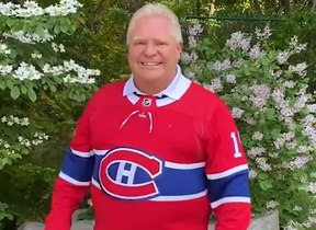 Ontario Premier Doug Ford dons a Guy Lafleur jersey as part of a bet with his Quebec counterpart Francois Legault after the Maple Leafs lost their series with the Habs.