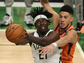 Jrue Holiday of the Milwaukee Bucks is defended by Devin Booker of the Phoenix Suns during the second half in Game 4 of the NBA Finals at Fiserv Forum on July 14, 2021 in Milwaukee, Wisc.