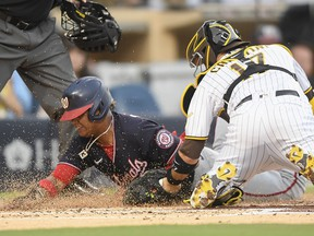 Starlin Castro of the Washington Nationals is tagged out at the plate by Victor Caratini of the San Diego Padres at Petco Park on July 6, 2021 in San Diego.