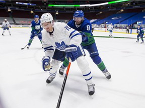 Vancouver Canucks forward J.T. Miller (9) checks Toronto Maple Leafs forward Zach Hyman (11) in the third period at Rogers Arena on March 6.