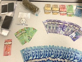 In this handout photo, Burnaby police showcase a stash of suspected drugs, cash and cell phones they seized from suspects.