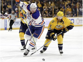 Edmonton Oilers center Connor McDavid (97) is defended by Nashville Predators' Ryan Ellis (4) during the first period of an NHL hockey game Thursday, Feb. 2, 2017, in Nashville, Tenn.
