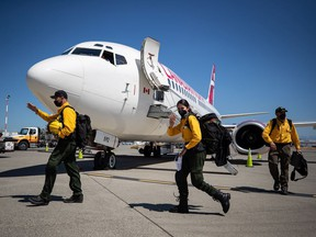 Firefighters from Mexico walk across the aircraft parking area after arriving on a charter flight in Abbotsford on Saturday, July 24, 2021. Firefighters will assist B.C. as the province deals with hundreds of wildfires burning in the province. They will undergo rapid COVID-19 testing and then be deployed to the Interior where they will stay in several bubbles separate from the more than 3,000 firefighters already working.