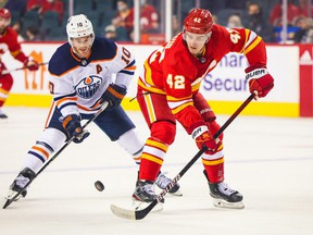Calgary Flames center Glenn Gawdin (42) and Edmonton Oilers center Derek Ryan (10) battle for the puck during the first period at Scotiabank Saddledome.