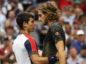 Carlos Alcaraz, left, of Spain meets at the net after defeating Stefanos Tsitsipas of Greece during his Men's Singles third round match on Day 5 at USTA Billie Jean King National Tennis Center on Sept. 3, 2021 in New York City.