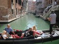 Tourists ride on a gondola as the municipality prepares to charge them up to 10 euros for entry into the lagoon city, in order to cut down the number of visitors, in Venice, Italy, Sept. 5, 2021.