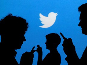 People holding mobile phones are silhouetted against a backdrop projected with the Twitter logo in this illustration picture taken Sept. 27, 2013.