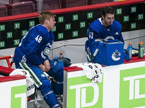 Olli Juolevi (left), seen after a conditioning skate in January before last season, has dropped below the likes of Quinn Hughes (right) in the Canucks' defensive pecking order. Word is he's being shopped around the league by Vancouver.