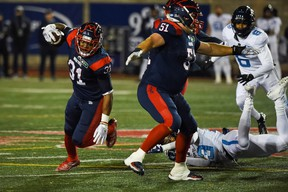 Alouettes running back William Stanback avoids a tackle by Argonauts' Jeff Richards in the second quarter during a Canadian Football League game at Molson Stadium.