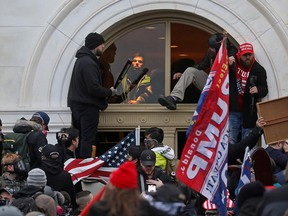 A mob of supporters of U.S. President Donald Trump climb through a window they broke as they storm the U.S. Capitol Building in Washington, Jan. 6, 2021.