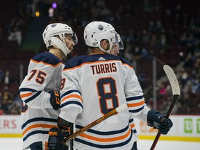 Edmonton Oilers defenceman Evan Bouchard (75) and forwards Ryan Nugent-Hopkins (93) and Kyle Turris (8) celebrate Bouchard's goal against the Vancouver Canucks at Rogers Arena on Saturday, Oct. 9, 2021.