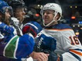 Edmonton Oilers forward Tyler Benson (16) gets into a scrum after the whistle with Vancouver Canucks forward Conor Garland (8) at Rogers Arena on Oct 9, 2021.