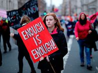 Climate activists hold placards as they march during a protest organized by the climate change action group Extinction Rebellion, in London, on February 22, 2020.