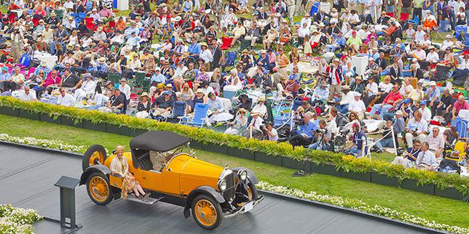 A 1921 Paige 6-66 Daytona Speedster crosses the awards ramp as spectators await the Best of Show announcement.