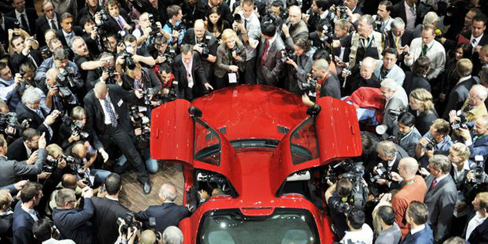 A crowd of journalists surround Daimler CEO Dieter Zetsche (at the left side of the car) presenting a Mercedes-Benz SLS AMG car during the 63rd International Motor Show (IAA) in the central German city of Frankfurt am Main on September 15, 2009.