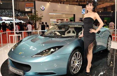 """A model poses next to the Lotus """"Evora"""", which is based on the first all-new vehicle platform from Lotus since the release of the Lotus Elise in 1995, at the Tokyo Motor Show."""